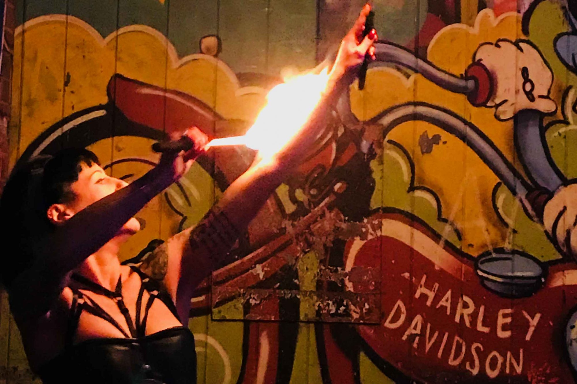 Fire-eater in front of wall graffiti