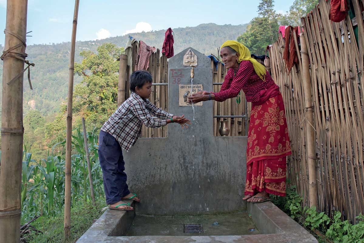 Image of a boy and his grandmother at a well